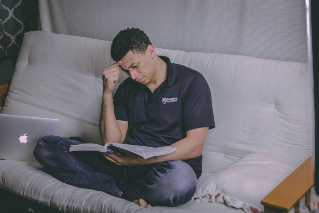 man sitter fundersam i sängen och studerar